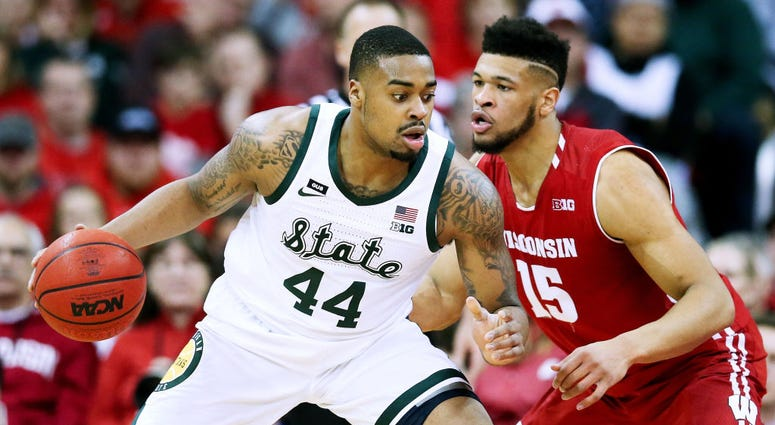Photo of Wisconsin player guarding a Michigan State player.