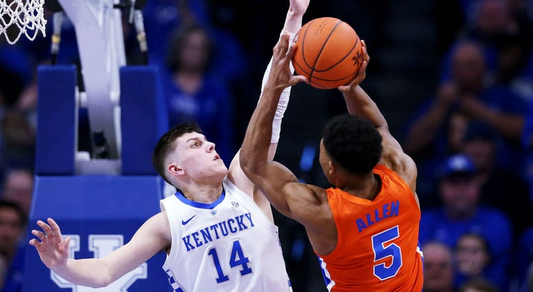 Photo of a Kentucky player trying to block the Florida player's shot.