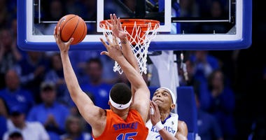 Photo of a Kentucky player contesting a possible dunk at the rim by a Florida player.