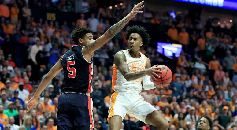 Photo of a Tennessee player being guarded by an Auburn player.