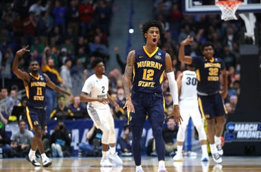A photo of a Murray State player celebrating with a couple of teammates and Marquette players in the background.