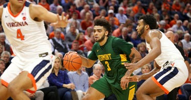 Photo of a Vermont player trying to dribble past a Virginia player.