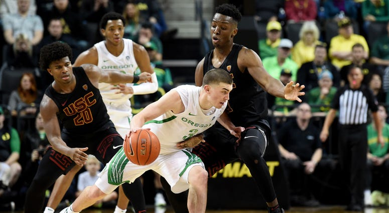 Photo of an Oregon player being guarded by an USC player.