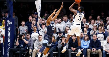 Photo of a Butler player taking a jumpshot over a Villanova player.