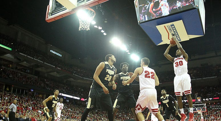 Photo of a Wisconsin player taking shot by two Purdue defenders.