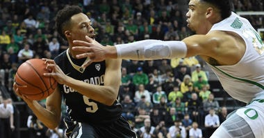 Photo of a Colorado player being guarded by an Oregon player.
