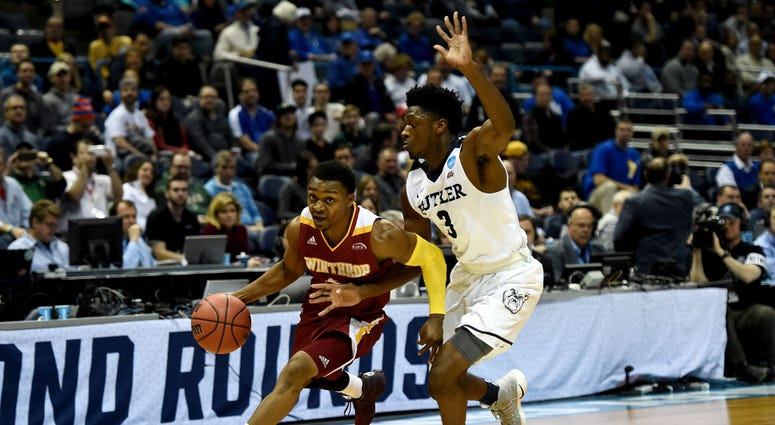 Photo of a Winthrop player trying to dribble past a Butler player.