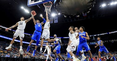 Photo of a Memphis and Cincinnati players going up for a rebound.