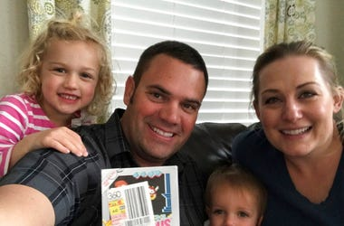"In this June 15, 2019 photo provided by Heritage Auctions, Scott Amos, along with his wife, Kristy, and daughters Grace, left, and Katie, pose in Reno, Nev., with an unopened copy of a 1987 cult-classic video game ""Kid Icarus."" The boxed game cartridge, s"