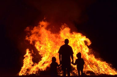 Man and children in silhouette watching the flames of a huge b