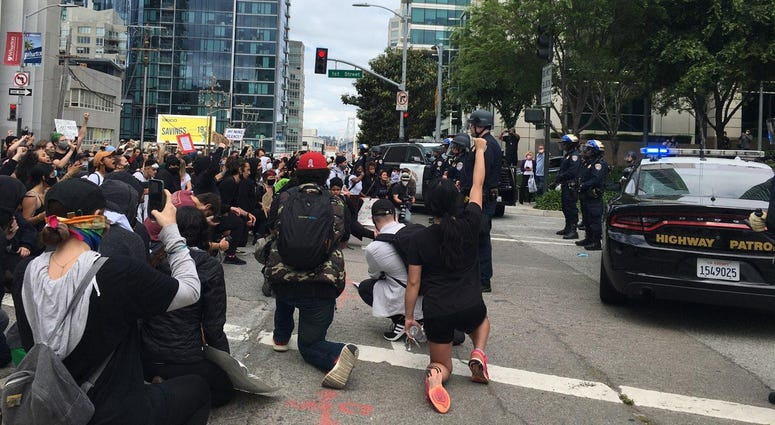 Protesters kneel in front of police at a San Francisco rally.