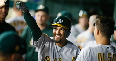 Apr 23, 2018; Arlington, TX, USA; Oakland Athletics shortstop Marcus Semien (10) smiles in the dugout after hitting a go ahead home run in the ninth inning against the Texas Rangers at Globe Life Park in Arlington. Mandatory Credit: Ray Carlin-USA TODAY S