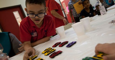 MCALLEN, July 14, 2014 (Xinhua) -- Children play with toy cars at the Catholic Charities center in Mcallen, Texas, the United States on July 13, 2014. More than 52,000 unaccompanied minors have been apprehended for illegally crossing into the United State