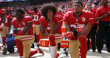 From left, The San Francisco 49ers' Eli Harold (58), Colin Kaepernick (7) and Eric Reid (35) kneel during the national anthem before their a game against the Dallas Cowboys on October 2, 2016, at Levi's Stadium in Santa Clara, Calif. (Photo by Nhat V. Mey