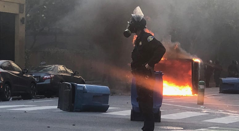 An officer stands alone as a dumpster burns in the background.