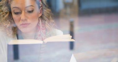 Woman reading book seen through cafe window...