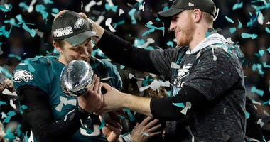 Philadelphia Eagles quarterback Carson Wentz, right, hands the Vincent Lombardi trophy to Nick Foles
