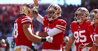 San Francisco 49ers tight end Garrett Celek, left, is greeted by quarterback Jimmy Garoppolo, center, after scoring a touchdown