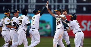 Oakland Athletics' Matt Olson (28) is congratulated by teammates