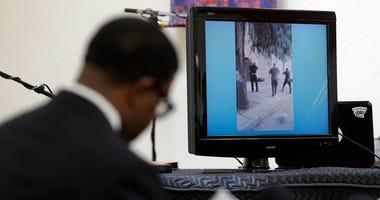 In this Jan. 18, 2016 file photo, attorney Adante D. Pointer, left, speaks at a news conference in San Francisco as a video is displayed of the San Francisco police shooting of Mario Woods, who police say appeared to raise a knife and approach one of the