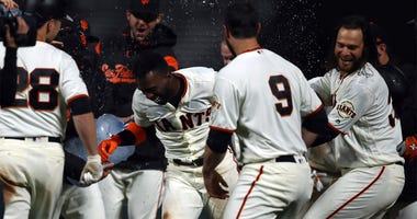 San Francisco Giants' Andrew McCutchen, second from left, is mobbed by teammates including Brandon Belt (9) and Buster Posey (28) after making the game-winning hit in the ninth inning of a baseball game against the Arizona Diamondbacks, Tuesday, April 10,