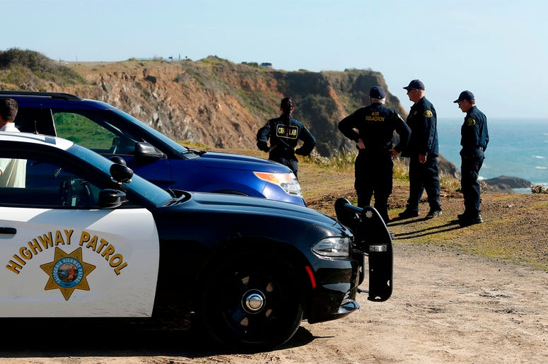 FILE - In this March 28, 2018, file photo, California Highway Patrol officers and deputy sheriffs from Mendocino and Alameda counties gather after a search for three missing children at the site where the bodies of Jennifer and Sarah Hart and three of the