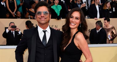 FILE - In this Jan. 21, 2018, file photo, John Stamos, left, and Caitlin McHugh arrive at the 24th annual Screen Actors Guild Awards at the Shrine Auditorium & Expo Hall in Los Angeles. Stamos announced on Instagram the birth of his son, Billy Stamos. (Ph