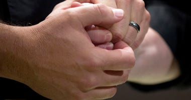 In this June 26, 2015, file photo, a couple holds hands during their wedding ceremony in Atlanta. In a report released on Wednesday, April 18, 2018, researchers found that melanoma patients who are married tend to be diagnosed at an earlier more treatable