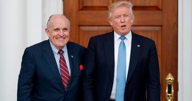 In this Nov. 20, 2016, file photo, then-President-elect Donald Trump, right, and former New York Mayor Rudy Giuliani pose for photographs as Giuliani arrives at the Trump National Golf Club Bedminster clubhouse in Bedminster, N.J. Giuliani is joining the