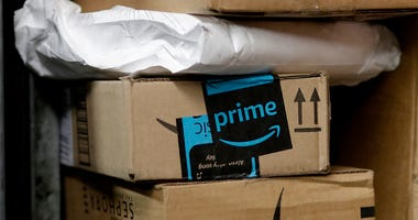 In this May 9, 2017, file photo, a package from Amazon Prime is loaded for delivery in New York. Last year, the online retailer introduced a system for letting people delivering packages into customers' homes. Now, it's their cars. GM says more than 7 mil
