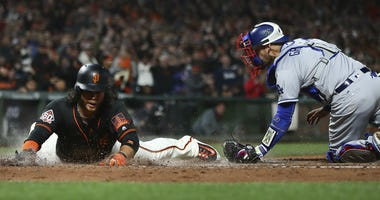 San Francisco Giants' Brandon Crawford, left, slides to score past Los Angeles Dodgers catcher Yasmani Grandal