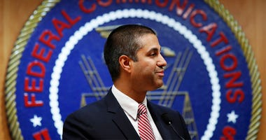 In this Dec. 14, 2017, file photo, after a meeting voting to end net neutrality, Federal Communications Commission (FCC) Chairman Ajit Pai smiles while listening to a question from a reporter in Washington. The FCC has set June 11 as the repeal date for ""