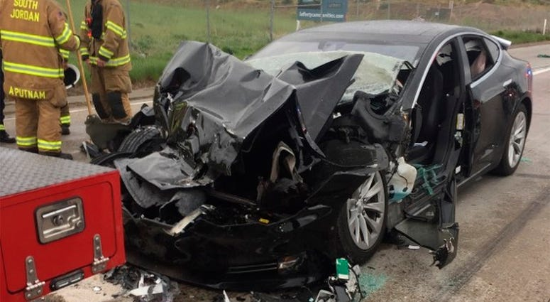 In this Friday, May 11, 2018, photo released by the South Jordan Police Department shows a traffic collision involving a Tesla Model S sedan with a Fire Department mechanic truck stopped at a red light in South Jordan, Utah. Witnesses indicated the Tesla