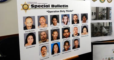 """A poster showing photos of suspects, some of whom remain at large, is seen at a news conference to announce indictments against the Mexican Mafia in Los Angeles Wednesday, May 23, 2018. Leaders of the notorious Mexican Mafia """"gang of gangs"""" were charged W"""
