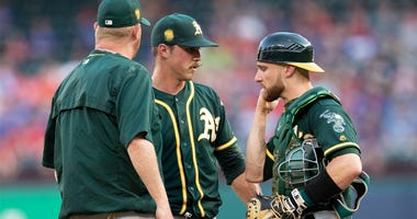Oakland Athletics starting pitcher Daniel Mengden, middle, meets on the mound with pitching coach Scott Emerson, left, and catcher Jonathan Lucroy after giving up back-to-back home runs to the Texas Rangers during the first inning of a baseball game Wedne