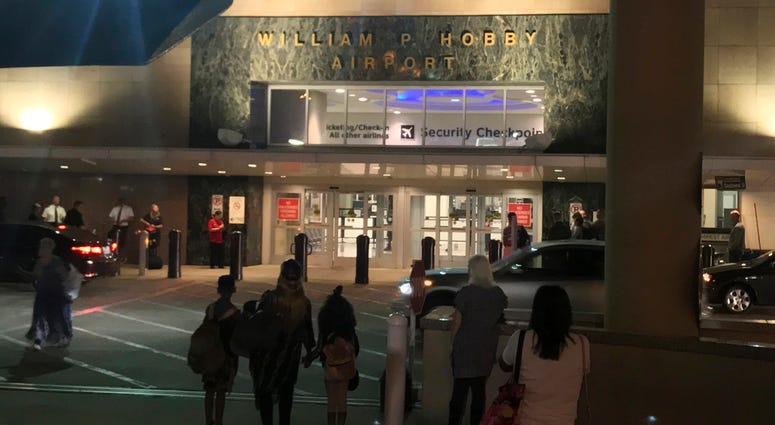 People wait outside Houston's William P. Hobby Airport on Thursday, June 7, 2018, after a toy grenade in a passenger's bag forced the shutdown of a security checkpoint, inconveniencing hundreds of people catching early-morning flights. (AP Photo/John L. M