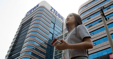 In this May 8, 2018, file photo, a woman passes by a ZTE building in Beijing, China. Chinese tech giant ZTE Corp.'s chairman promised no further compliance violations and apologized to customers in a letter Friday, June 8, 2018, for disruptions caused by