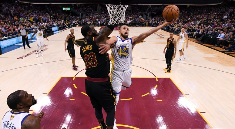 Golden State Warriors guard Stephen Curry (30 shoots around Cleveland Cavaliers forward LeBron James (23) in Game 4 of basketball's NBA Finals on Friday, June 8, 2018, in Cleveland. The Warriors defeated the Cavaliers 108-85 to sweep the series. (Gregory
