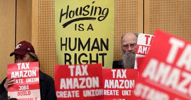 In this May 14, 2018 file photo, members of the public look on at a Seattle City Council before the council voted to approve a tax on large businesses such as Amazon and Starbucks to fight homelessness in Seattle. Seattle city leaders say Monday, June 11,
