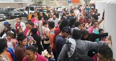 In this Monday, June 4, 2018 file photo, people seeking political asylum in the United States line up to be interviewed in Tijuana, Mexico, just across the U.S. border south of San Diego. Immigration judges generally cannot consider domestic and gang vio