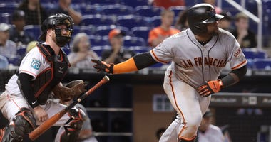 San Francisco Giants' Pablo Sandoval, right, watches after hitting an RBI single to score two runs during the 16th inning of a baseball game against the Miami Marlins, Thursday, June 14, 2018, in Miami. The Giants won 6-3 in 16 innings. At left is Miami M