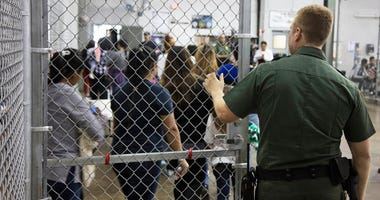 In this photo provided by U.S. Customs and Border Protection, a U.S. Border Patrol agent watches as people who've been taken into custody related to cases of illegal entry into the United States, stand in line at a facility in McAllen, Texas, Sunday, June