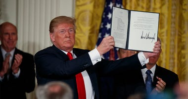 """President Donald Trump shows off a """"Space Policy Directive"""" after signing it during a meeting of the National Space Council in the East Room of the White House, Monday, June 18, 2018, in Washington."""