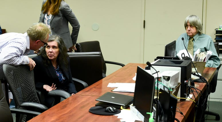 In this May 4, 2018, file photo, defendant Louise Anna Turpin, second left, talks with an investigator as her husband David Allen Turpin, right, looks on during a court appearance in Riverside, Calif. David and Louise Turpin are scheduled to appear for a