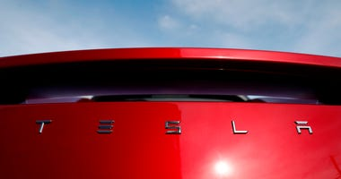 In this April 15, 2018, file photo, the sun shines off the rear deck of a roadster on a Tesla dealer's lot in the south Denver suburb of Littleton, Colo. Tesla is suing a former employee at its Nevada battery factory alleging that he hacked into the manuf