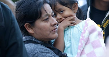 Catalina Ventura, a migrant worker from Fresno, holds her daughter Celeste, 3, as they joined more than 100 others demonstrating outside the federal courthouse where a federal judge will hear arguments over the U.S. Justice Department's request to block t