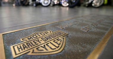 In this April 26, 2017, file photo, rows of motorcycles are behind a bronze plate with corporate information on the showroom floor at a Harley-Davidson dealership in Glenshaw, Pa. Harley-Davidson, facing rising costs from new tariffs, will begin shifting
