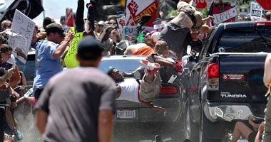 In this Aug. 12, 2017, file photo, people fly into the air as a vehicle is driven into a group of protesters demonstrating against a white nationalist rally in Charlottesville, Va. Federal hate crime charges have been filed against James Alex Fields Jr.,