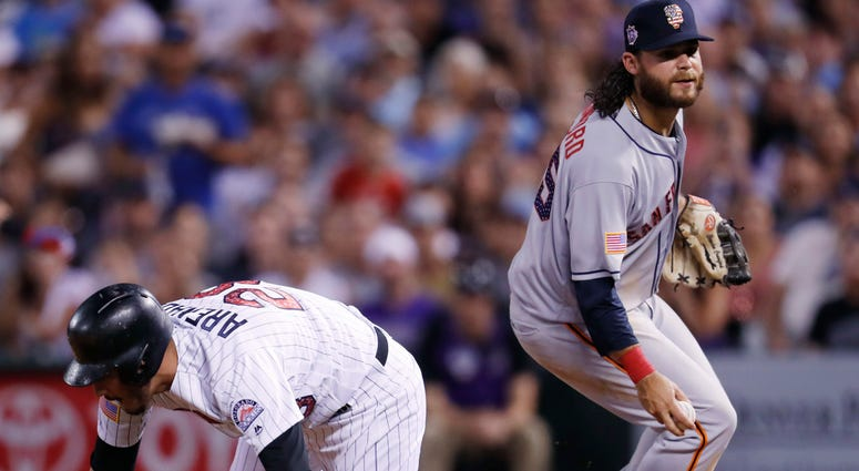 Colorado Rockies' Nolan Arenado, left, falls down after being caught in a rundown between first and second bases by San Francisco Giants shortstop Brandon Crawford in the seventh inning of a baseball game Monday, July 2, 2018, in Denver. (AP Photo/David Z