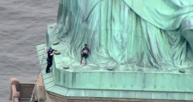 In this image made from video by PIX11, a person, center, leans against the robes of the Statue of Liberty on Liberty Island, as one of the police officers climbed up on a ladder to stand on a ledge nearby talking the climber into descending in New York,